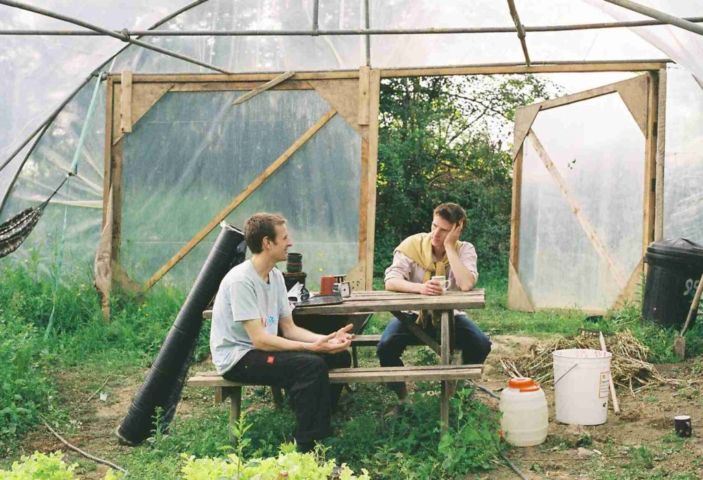 Andrew and a friend in a permaculture garden in the UK.