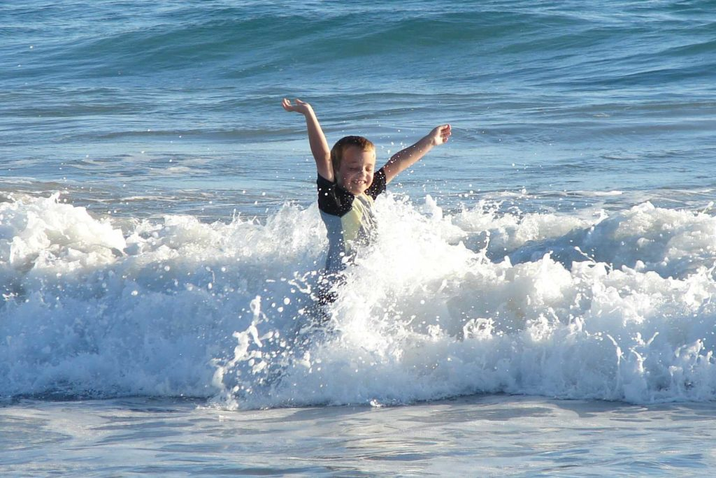 Sam as a child frolicking in the waves at Port Gregory.