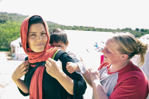 A Carry the Future volunteer fits a Syrian mother with a baby carrier.