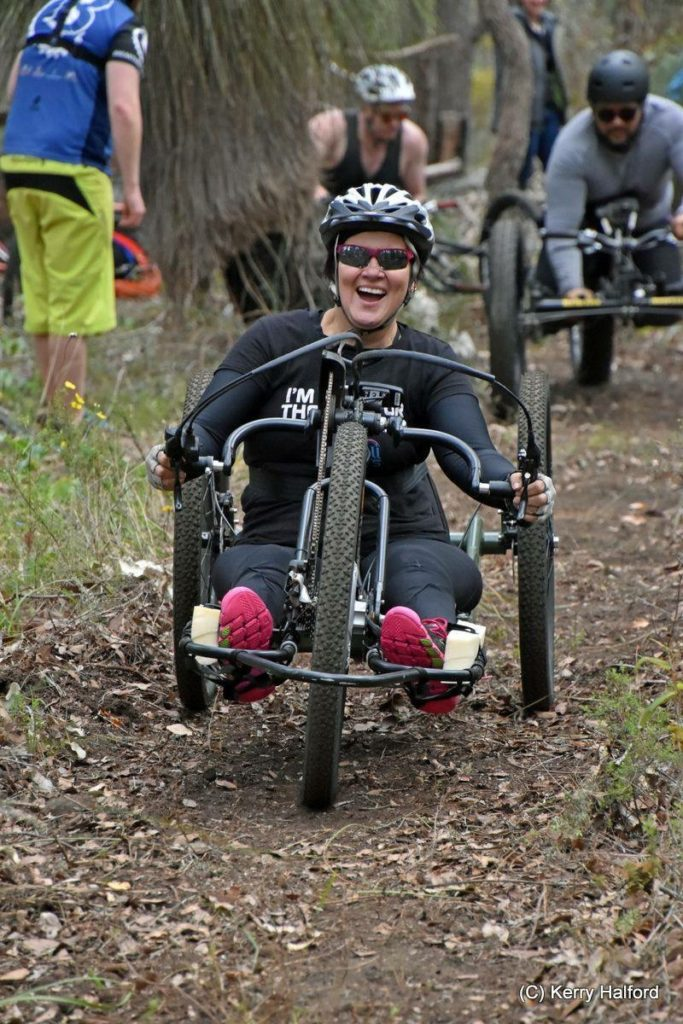 a woman is in a handcycle riding in the forest. she is smiling broadly.