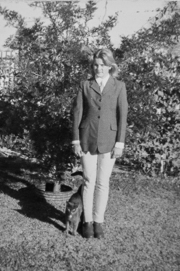 a young woman is standing up straight, she is wearing a horseriding kit of jodphurs, a riding jacket and shirt