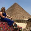 imgae of woman sitting on a camel in front of a pyramid in Egypt