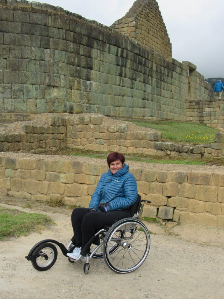 a woman is sitting in a wheelchair in front of an ancient incan ruin, she is wearing a blue jacket to keep warm.