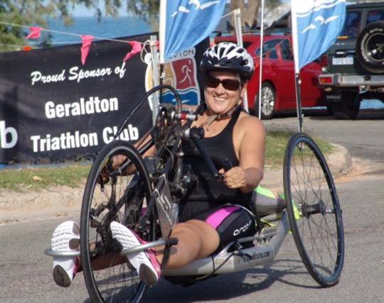 a woman is on a adapted handcycle. She is in front of a sign that says geraldton triathlon club.