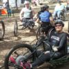 a woman sitting in a adapted mountain bike smiling at the camera.