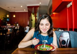 a woman with black hair is about to eat a mouthful of food, she is in a restaurant and has a smile on her face. She is wearing a blue sleeveless dress