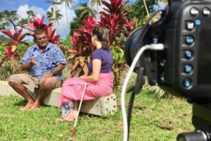 a man in a floral shirt and a woman in a pink skirt and blue t shirt sit next to each other on a grass area in front of some tropical plants with bright red flowers. A camera lense is visible in the foreground.