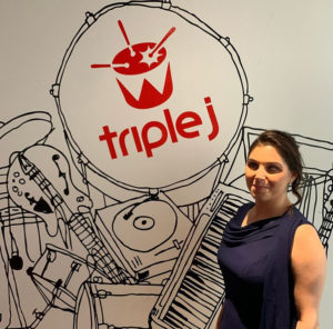 a woman is standing in front of a sign that says Triple J. She is wearing a blue sleeveless dress and is smiling at the the camera