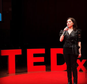 a woman in standing on a stage in front of a red sign that says TED x . She is wearing a black shirt and pants and is speaking into a microphone