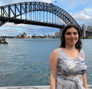 A woman is wearing a light blue dress, she has black hair, she is smiling at the camera and the sydney harbour bridge is in the background