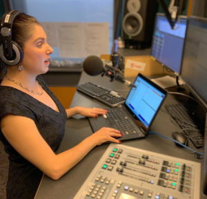 a woman wearing headphones is sitting in front of a desk with a keyboard and a microphone. It is in a recording studio.