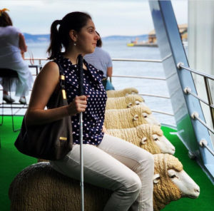 a woman wearing a polka dot shirt and white pants sits on a deck of a ship on a seat shaped like a sheep. it is one of a row of sheep statues lined up on the deck looking out to sea. She is holding a white cane by her side.